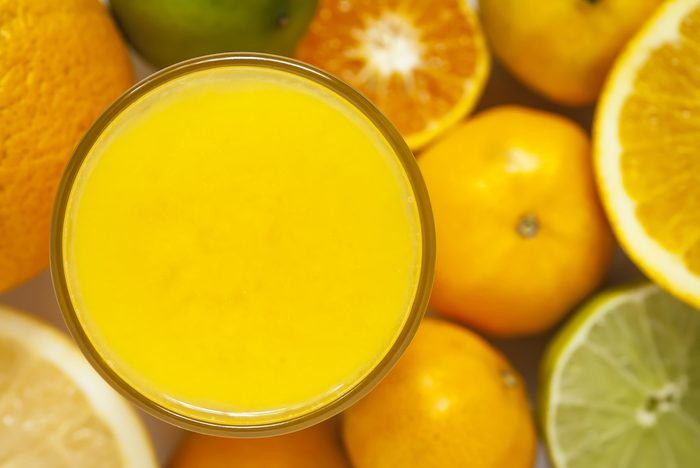 glass of orange juice surrounded by citrus fruits