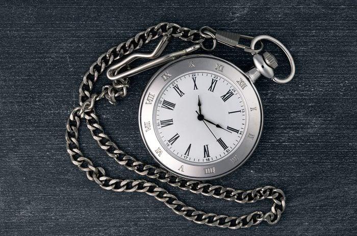 Shiny silver chain watch on a black chalkboard background
