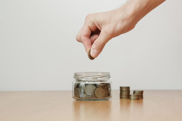 Hand putting coins in a jar