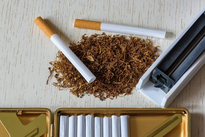 A pile of natural tobacco on a white wooden table, a device for manual production of cigarettes and cigarettes in a cigarette case. Smoking. Nicotine addiction. Health hazard.