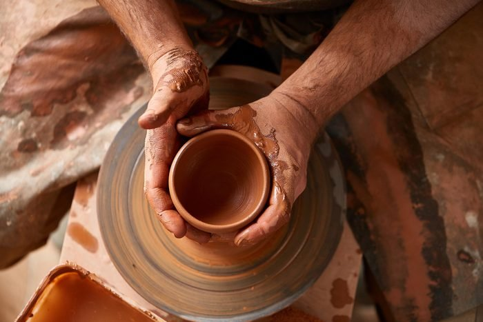 close up of hands working on a pottery wheel