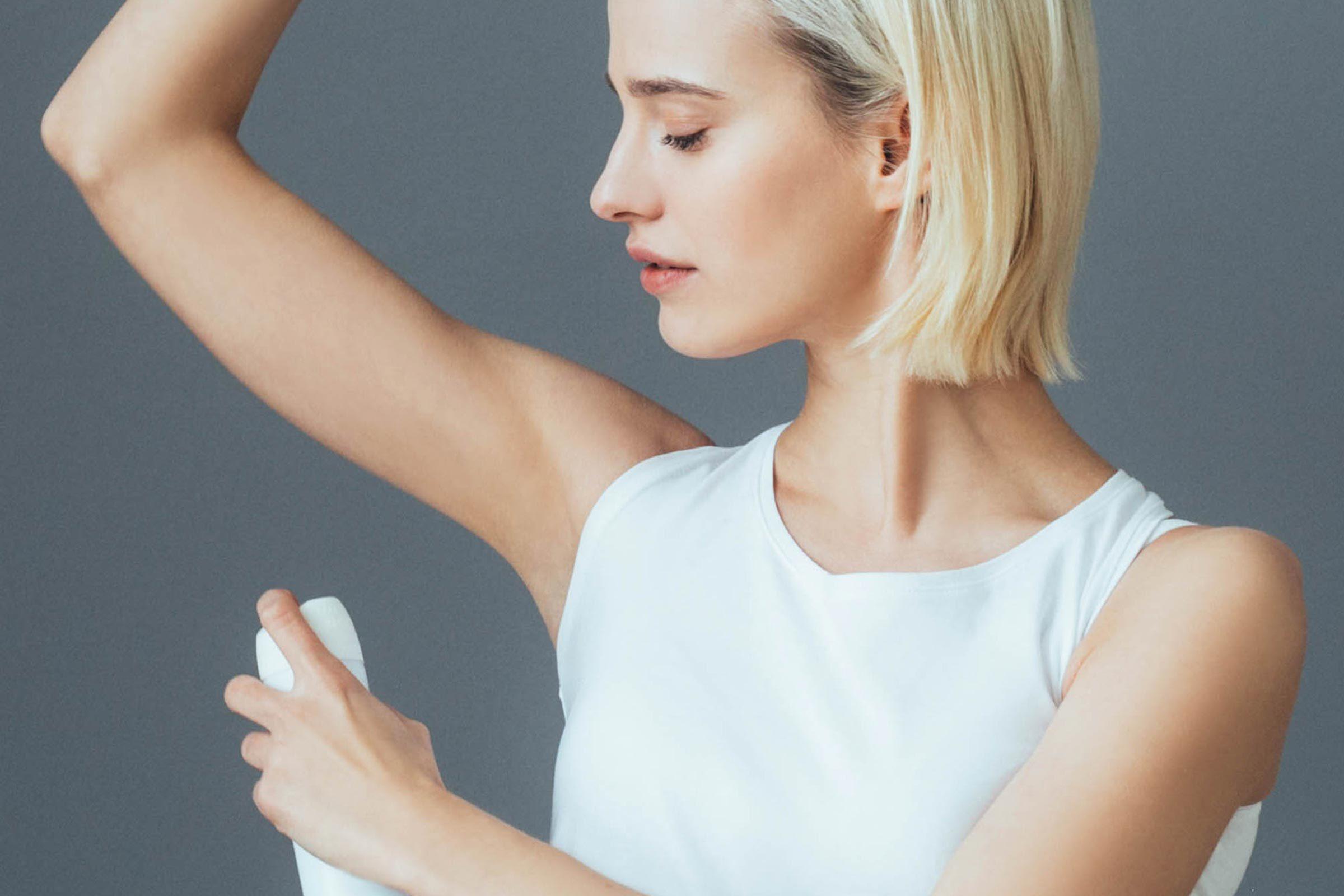 woman applying deodorant spray to armpit