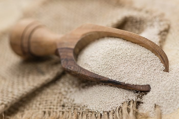 Heap of dried Yeast (detailed close-up shot) on wooden background