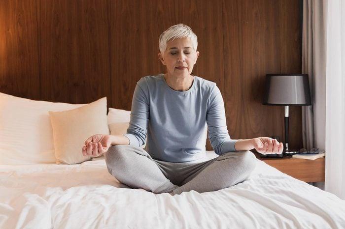 senior woman meditating on bed