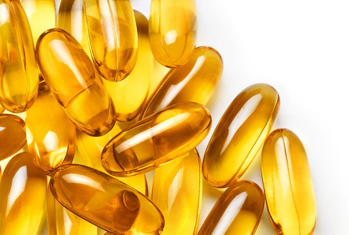 Pile of capsules Omega 3 on white background. Close up, top view, high resolution product.