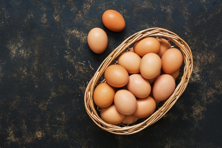 Brown eggs in a basket on an old dark surface. Top view, space for text