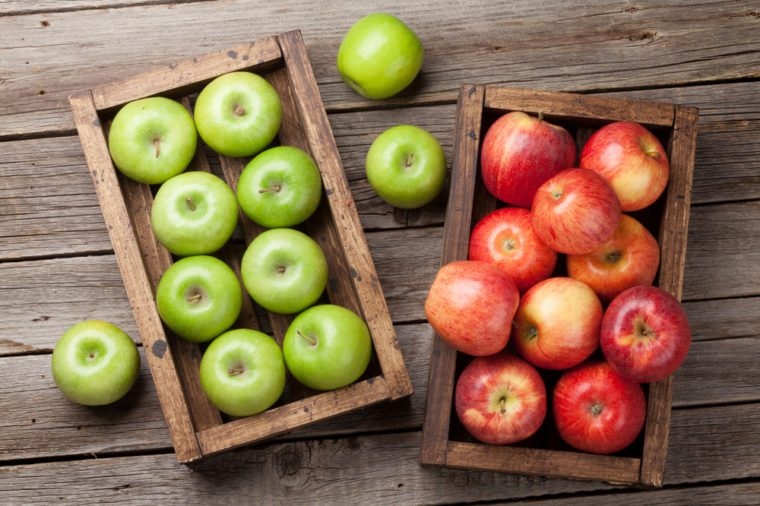 Ripe green and red apples in wooden box. Top view