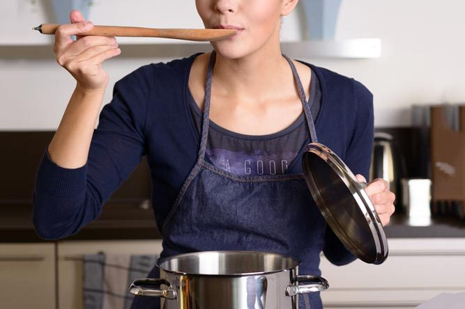 Young housewife tasting her cooking as she prepares the dinner in her kitchen sampling directly from the pot on the hob with a wooden spoon as she looks at the camera