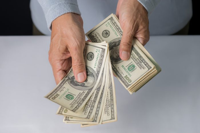 Man hand holding money,bribery concept. Business man giving stack of US dollar.