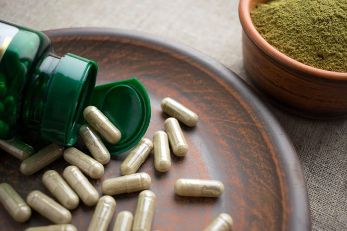 Close up Green capsules, bottle and powder on a clay brown plate on a burlap background. Dietary supplements for Weight Loss and detox. vitamins and minerals for vegans and vegetarians. Superfood
