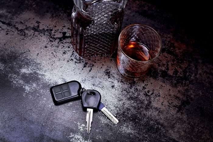 Luxury decanter of whiskey and a glass at the bar. Leisure concept, alcohol, alcoholic beverages. Strong brandy in a glass and car keys on a table in a bar or restaurant