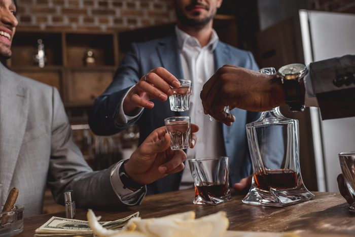 cropped shot of multiethnic men drinking alcohol together