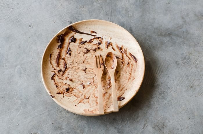 Dirty Plate, Spoon and Fork on cement background. Top View Text Space