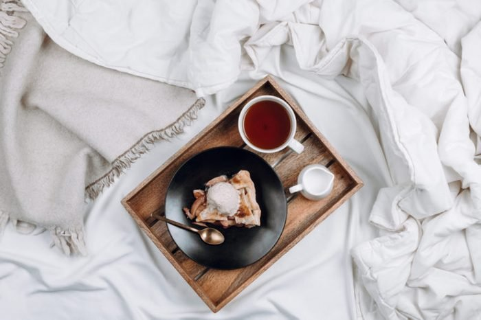 Cozy flatlay of bed with wooden tray with vegan apple pie, ice cream and black tea on white sheets and blankets