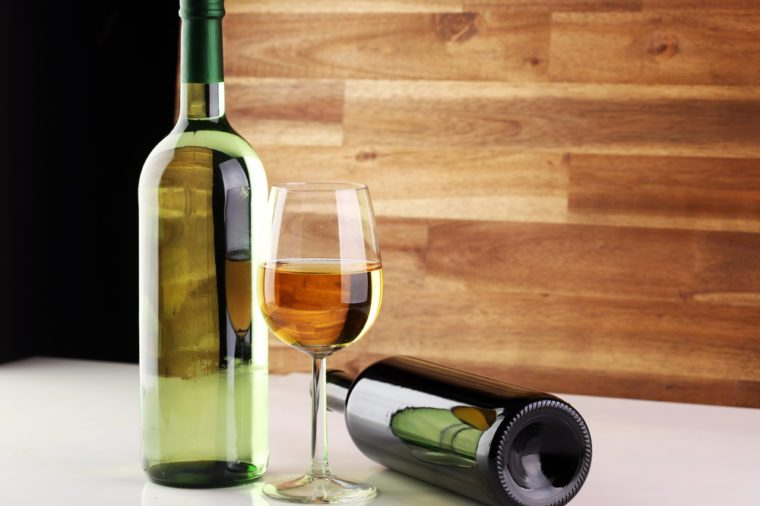 Bottle and glass of wine on white table
