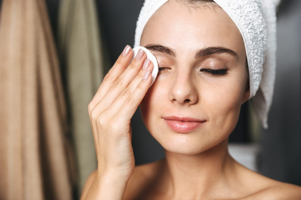 woman removing eye makeup with a cotton pad