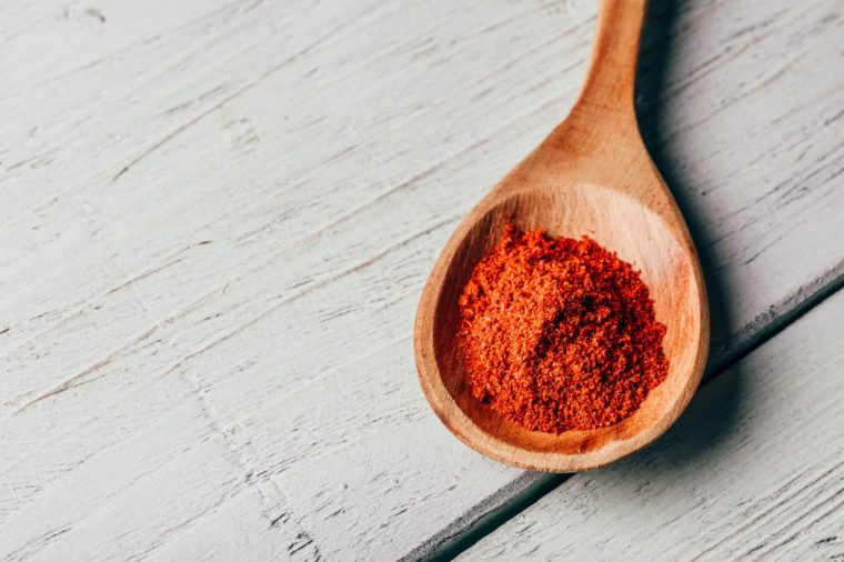Spoonful of red chili pepper powder in a wooden spoon on a white wooden table.