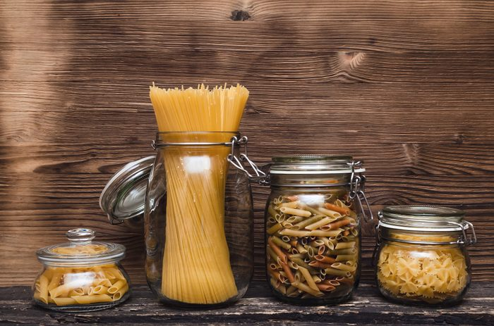 Pasta macaroni concept background. Pasta in a glass jar container.
