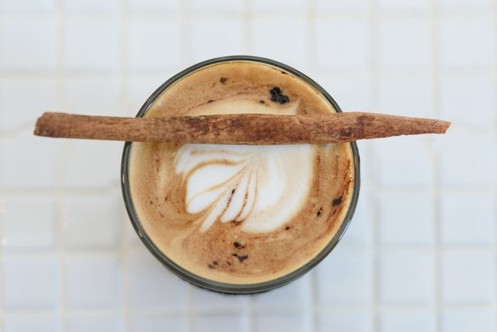 Cup of cappuccino art with cinnamon stick on top over marbel white table background,top view