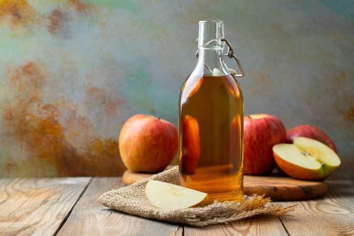 Apple vinegar. Bottle of apple organic vinegar or cider on wooden background. Healthy organic food. With copy space