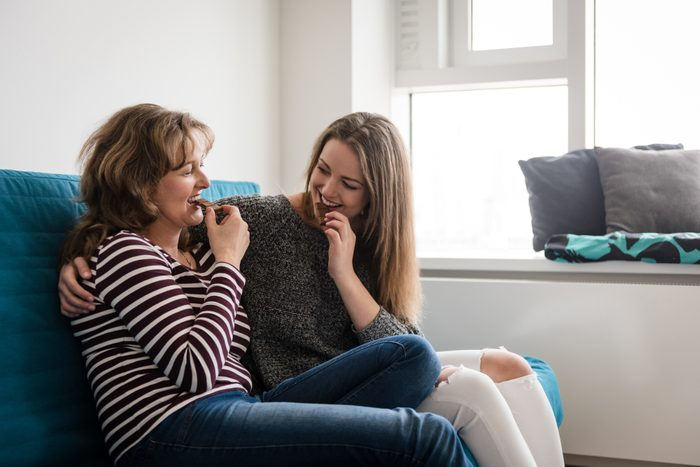 Mother and daughter biting off chocolate at home