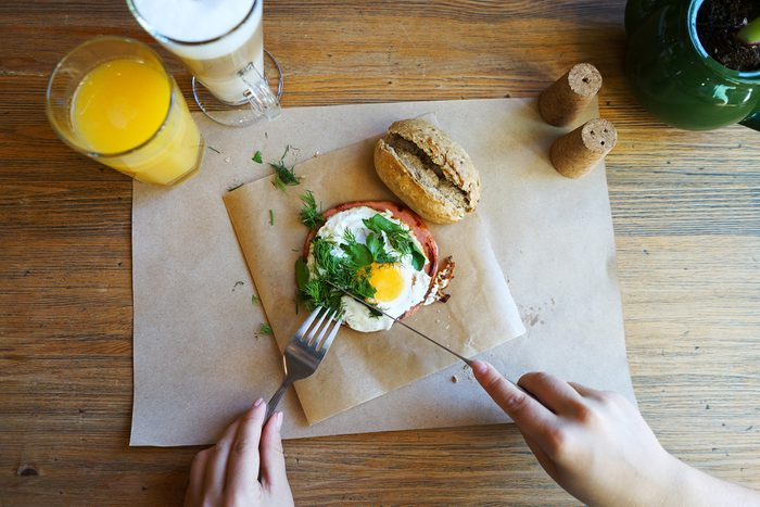 Hands of the girl cut the eggs on paper, served with bread, herbs, sausage and fresh juice.