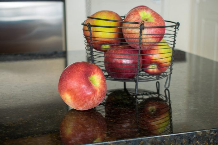 One apple beside a metal basket filled with red apples and strong reflections.