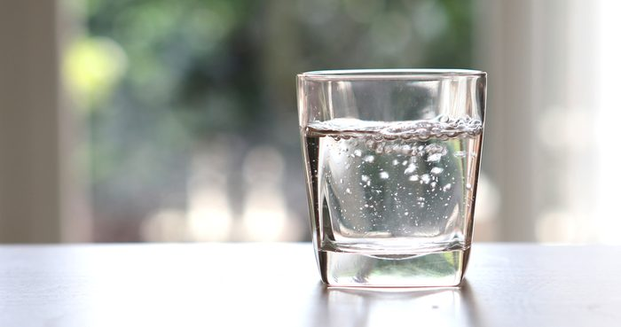 Close up the purified fresh drink water from the bottle on table in living room