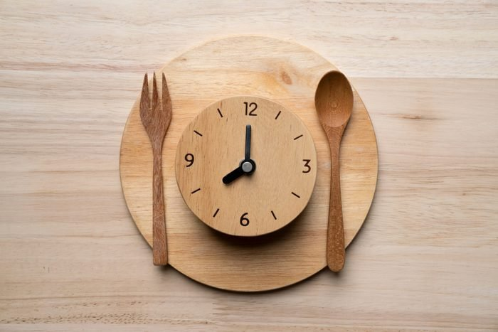 Food clock spoon and fork, Healthy food concept on wooden table background