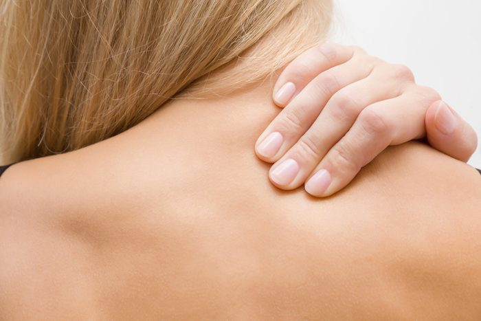 Young, blonde woman massaging her naked shoulder with hand. Pain from strain and incorrect posture. Inactive lifestyle.