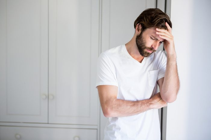 Worried man with hand on forehead leaning on wall at home