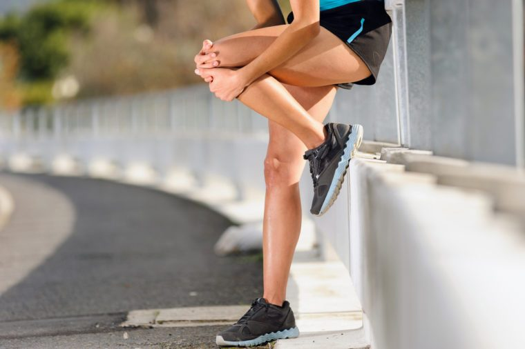 Woman in pain after hurting her leg while running outside.