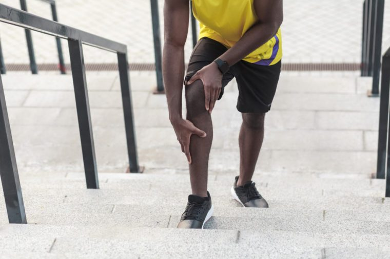 Man jogging up the stairs holding his knee.