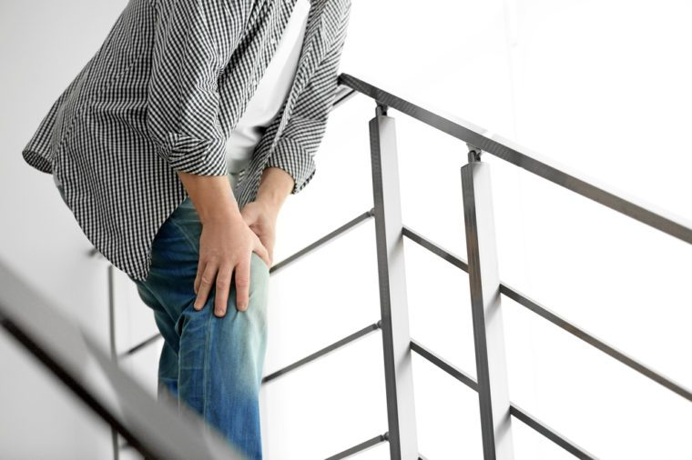 Man suffering from knee pain on the stairs.