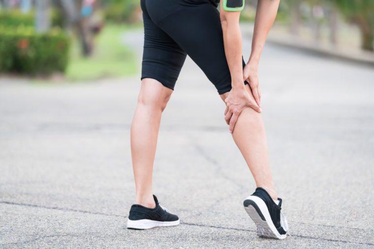 Woman runner with an injured leg outdoors.