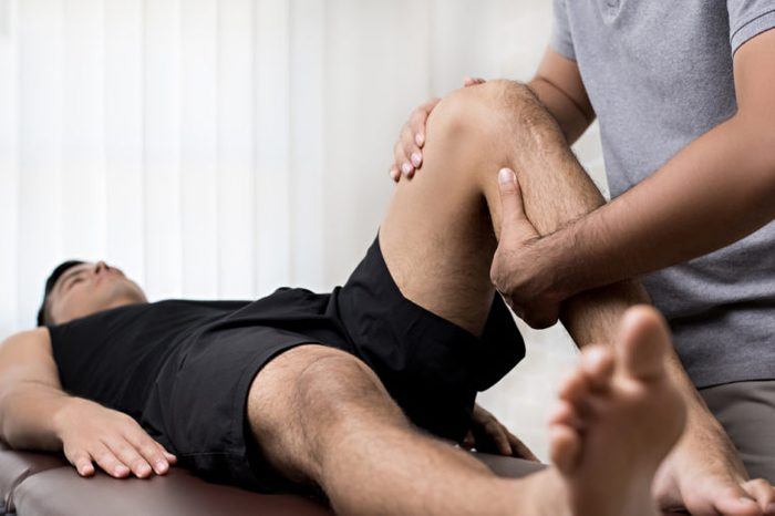 Therapist treating injured knee of athlete male patient.