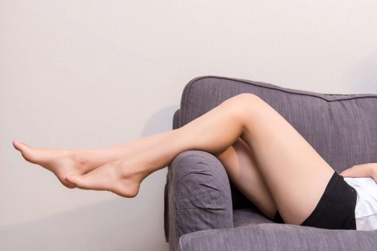 Woman's legs hanging off the edge of the sofa.