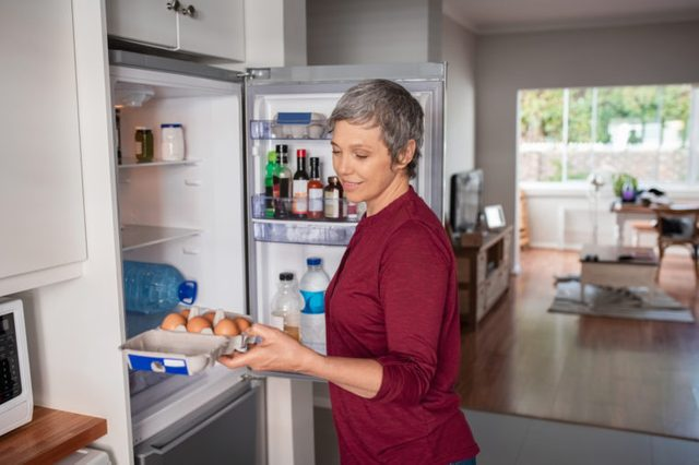 woman looking for food in refrigerator