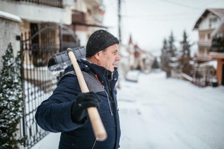 man prepared to shovel snow in winter