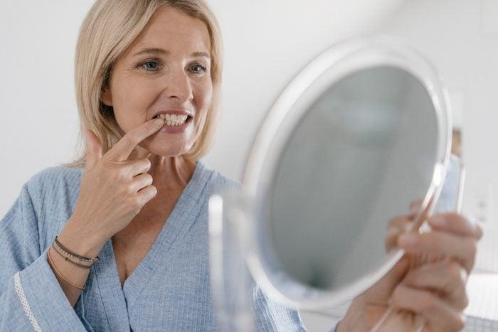 mature woman looking at teeth in handheld mirror