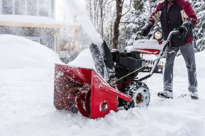 man using snowblower machine in winter to shovel snow