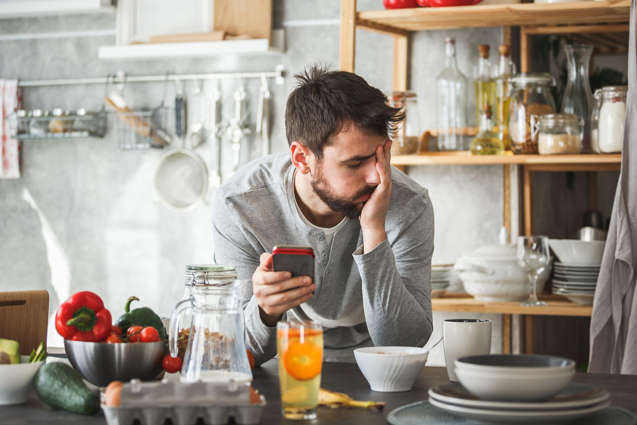 upset man at home in kitchen with his phone
