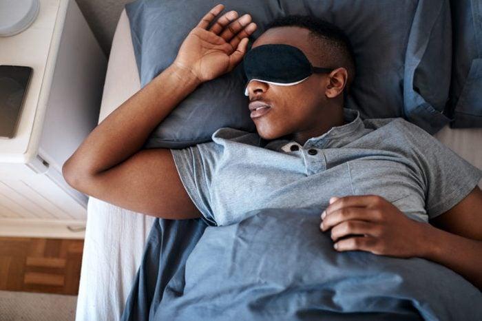 young man sleeping with sleeping mask over eyes