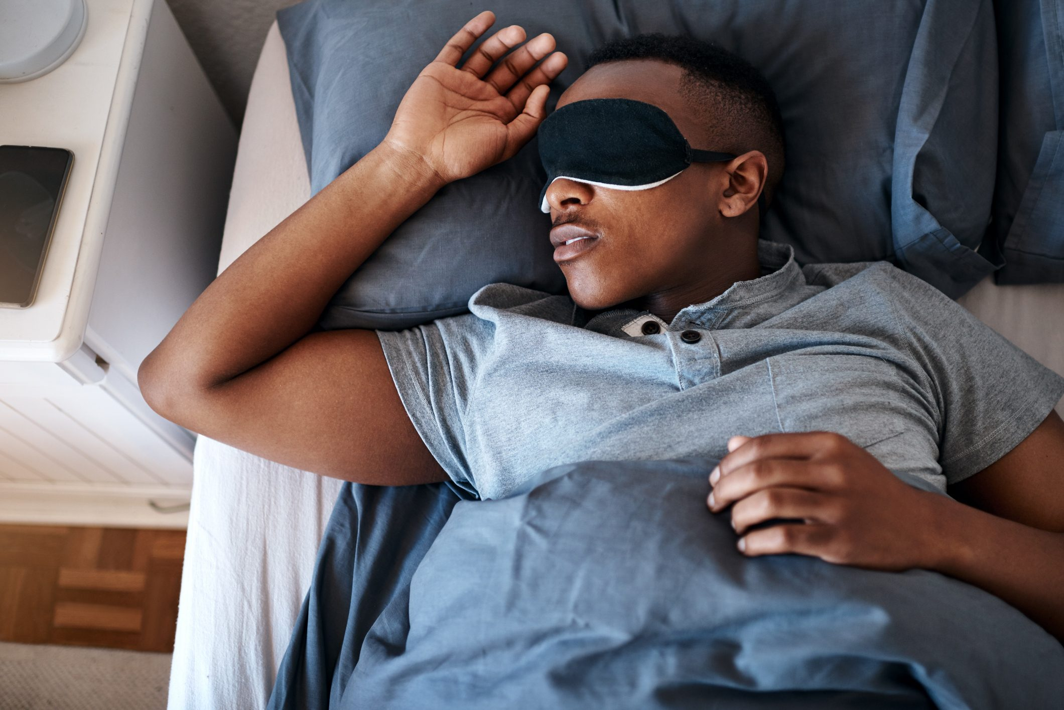 man sleeping in bed with eye mask on
