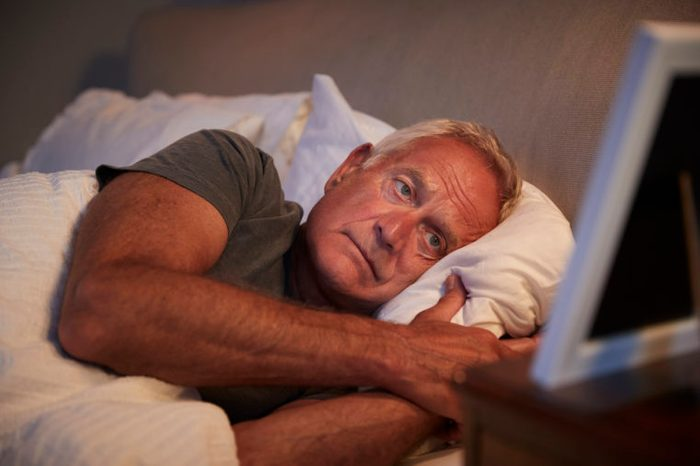 man laying awake in bed at night trying to sleep