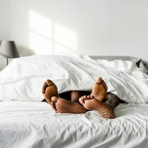 black couple laying in bed together focus on feet