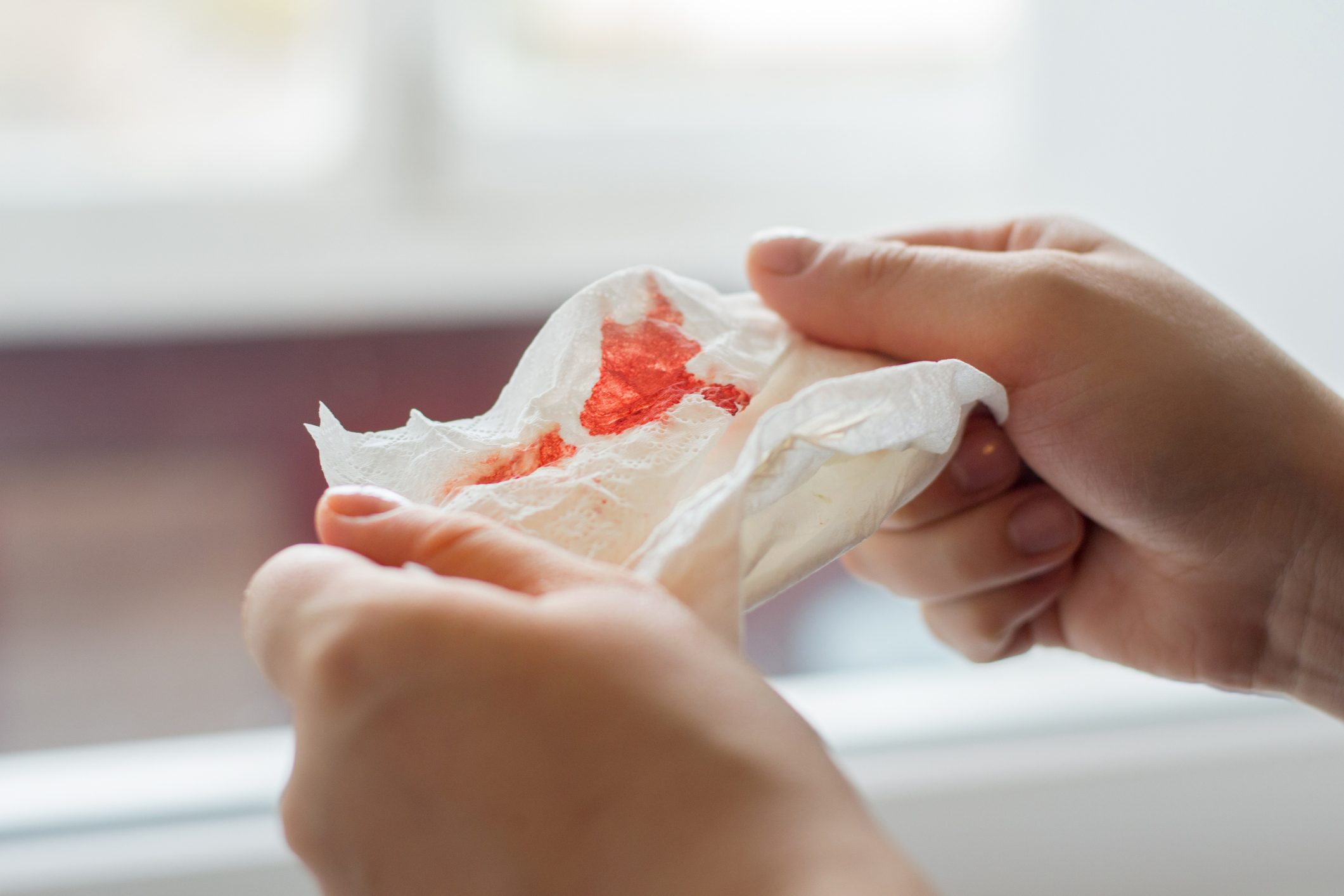 hands holding a bloody tissue