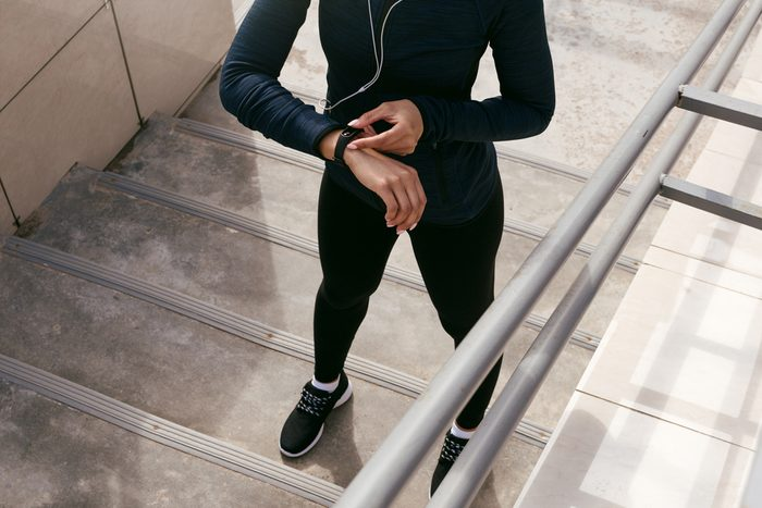 Unrecognizable female using fitness tracker after training