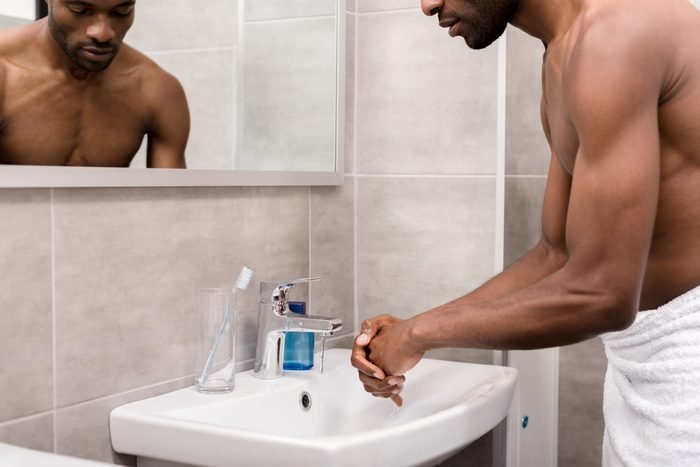 man in towel washing his hands