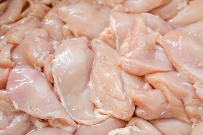 Chicken fillet. meat factory of chicken products. Butcher work.
